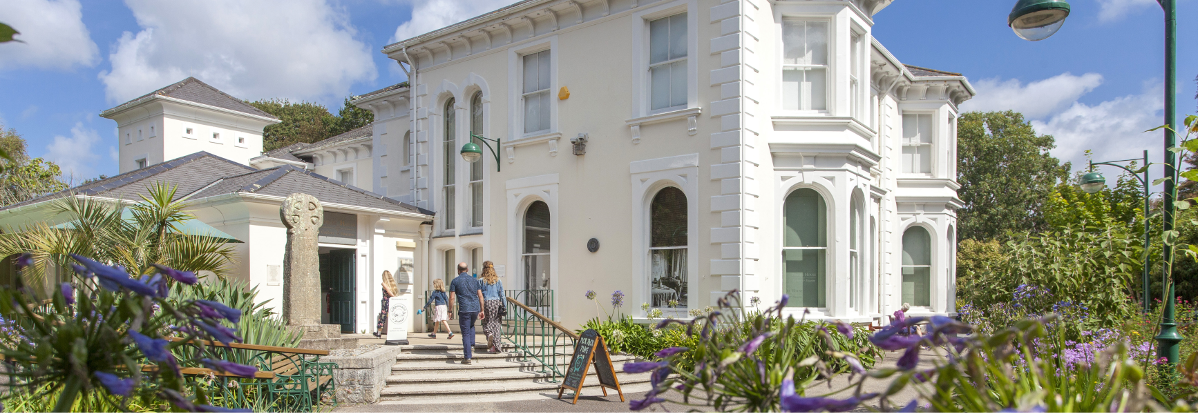 A family walks up the steps towards the entrance of Penlee House Gallery Museum